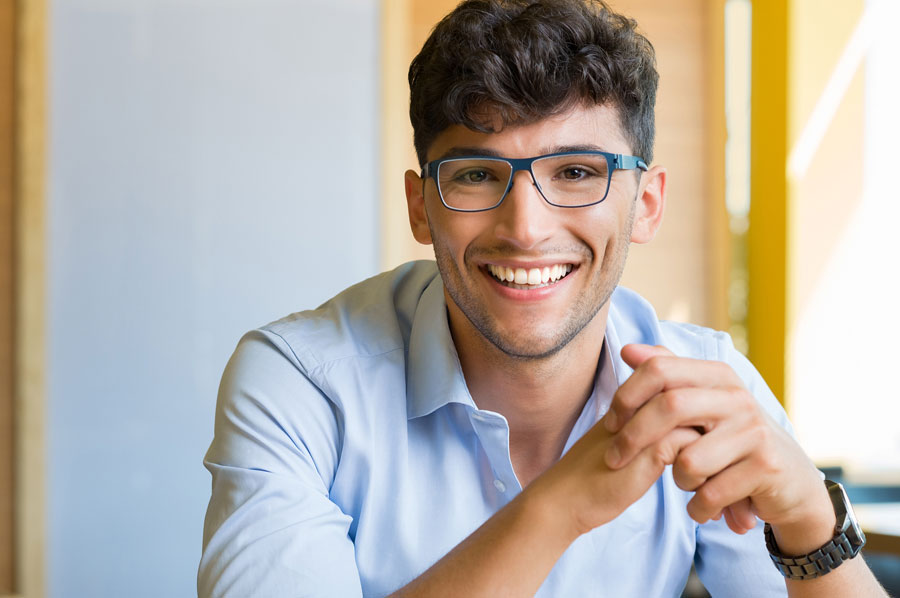 male college student sitting at desk smiling