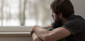 Depressed male man looking out the window Adult Counseling