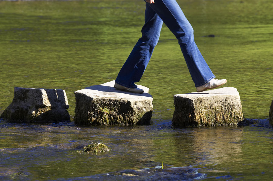 woman walking across stepping stones over a stream